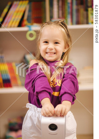 Adorable little girl shopping for toys. Cute female in toy store. Happy young girl selecting toy 58301879