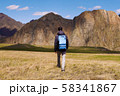 tourist in a cap and jacket with a backpack goes on the grass in the direction of mountains 58341867