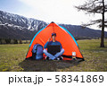 young man with a laptop sitting in a tent against the mountains and hills of Altai and talking on a 58341869