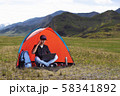 young man with a laptop sitting in a tent against the mountains and hills of Altai and talking on a 58341892