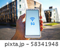 man hand holding a smartphone and 5g signal symbol on screen with broadcast antenna icon on city 58341948