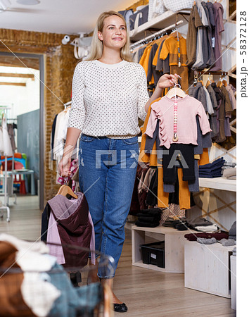 Woman holding hanger with baby clothes in showroom 58372128