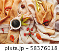 Cup of hot coffee with fallen leaves and berries on beige scarf. Folded warm accessory with autumn plants and tasty beverage. Top view, flat lay. 58376018