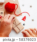 Woman is packing Christmas and New Year DIY presents in craft paper. Gifts tied with white and red threads. Boxes and star confetti on white background. 58376023