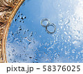 Pair of wedding rings on wet mirror surface with blue sky reflection. Close up photo with traditional jewelry of bride and groom. 58376025