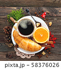 Christmas and New Year background with continental breakfast - cup of hot coffee with cinnamon, fresh orange and croissant. Decorations - snowflake, crochet napkin, pine cones. 58376026