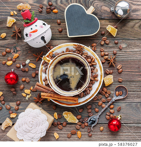 Rustic wooden background with cup of coffee and New Year decorations. Heart shaped chalkboard. Christmas beverage with ginger and anise. Top view, place for text. 58376027