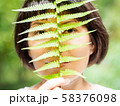 Young woman is hiding her eyes with fern leaf.  58376098