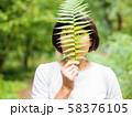 Young woman is hiding her eyes with fern leaf. 58376105
