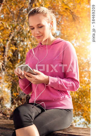 Healthy Lifestyle. Young woman in earphones sitting outdoors autumn background listening music 58469209