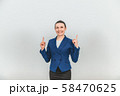 Smiling beautiful teacher standing, pointing her fingers up at the copy space for text or product 58470625