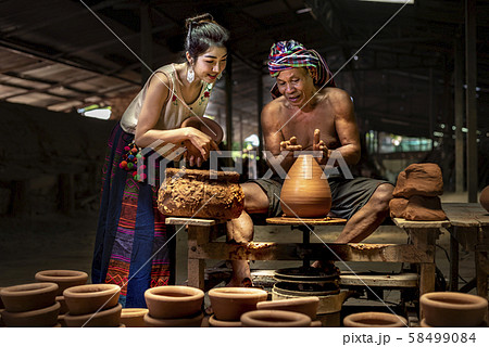 Asian young girl interesting how to Craftman making pottery from wet clay on wheel. 58499084