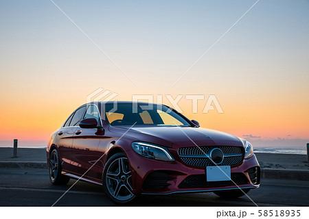 ワインレッドの車と朝焼けの海岸 58518935