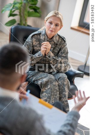 Mid-aged servicewoman listening to young psychoanalyst attentively 58583492