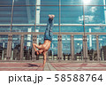 dancer in jump stands on one arm, acrobat actor break dance, hip-hop. In summer city, background 58588764