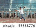 Dancer in motion dancing break dance, hip hop. In summer city, background glass windows clouds 58588770