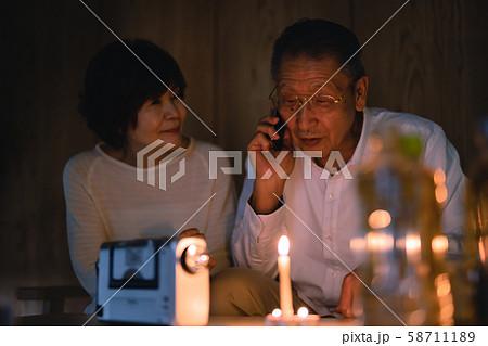 停電した部屋で台風がすぎるのを待つ夫婦 58711189