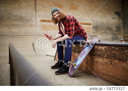 Contemporary Man Posing with Smartphone in Skating Park 58773327