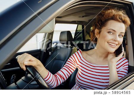 Cheerful girl making call at steering wheel stock photo 58914565