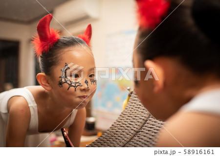 ハロウィンの仮装をして鏡を見る女の子 58916161