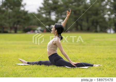 ヨガ 芝生公園でリラックス解放感 新体操のように柔らかい美しい体の女性 58975470