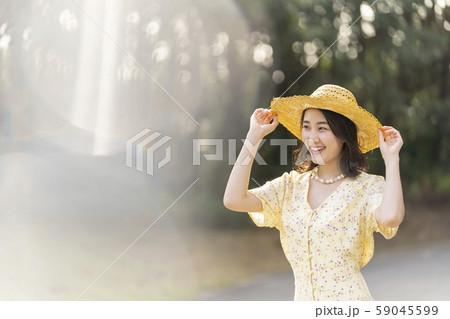 麦わら帽子で紫外線対策をして森林浴をする若い女性 59045599