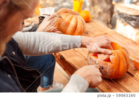 Young adult man and woman making jack-o-lantern pumpkin 59063160