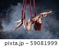 Female athletic, sexy and flexible aerial circus artist with redhead dancing in the air on the silk 59081999