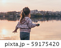 Little girl standing near big lake or river 59175420