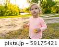 Little girl with funny emotional face with bread in hands 59175421