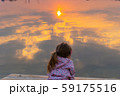 Sun reflection in water of lake or river and little girl 59175516