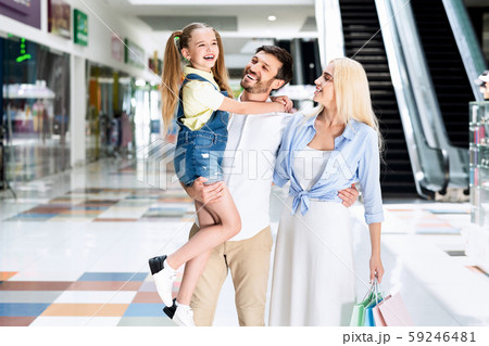 Man Carrying Daughter And Hugging Wife In Shopping Mall 59246481