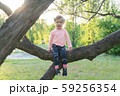 Sweet little kid girl sitting on the branch 59256354