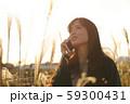 ススキの野原を音楽を聴きながら歩く女性 59300431