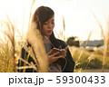 ススキの野原を音楽を聴きながら歩く女性 59300433