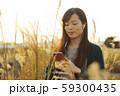 ススキの野原を音楽を聴きながら歩く女性 59300435