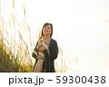 ススキの野原を音楽を聴きながら歩く女性 59300438