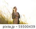 ススキの野原を音楽を聴きながら歩く女性 59300439