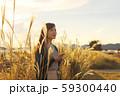 ススキの野原を音楽を聴きながら歩く女性 59300440