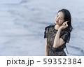 沖縄県石垣島の海辺波打ち際で貝殻を拾い波の音を聞く人魚のように美しい女性のライフスタイル 59352384