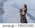沖縄県石垣島の海辺波打ち際で貝殻を拾い波の音を聞く人魚のように美しい女性のライフスタイル 59352385