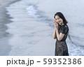 沖縄県石垣島の海辺波打ち際で貝殻を拾い波の音を聞く人魚のように美しい女性のライフスタイル 59352386