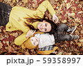 Young mother and baby lie on yellow leaves 59358997