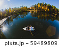 Beautiful young wedding couple on small boat sailing on a pond 59489809