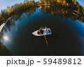 Beautiful young wedding couple on small boat sailing on a pond 59489812