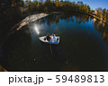 Beautiful young wedding couple on small boat sailing on a pond 59489813