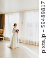 Bride standing alone with bridal bouquet near a big window 59489817
