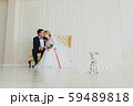 Bride and bridegroom sitting on a white sofa in the big white hall 59489818