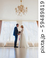 Bride and bridegroom standing near the big window 59489819
