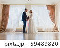 Bride and bridegroom standing near the big window 59489820